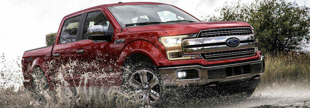 2018 Ford F-150 in red driving through a mud puddle