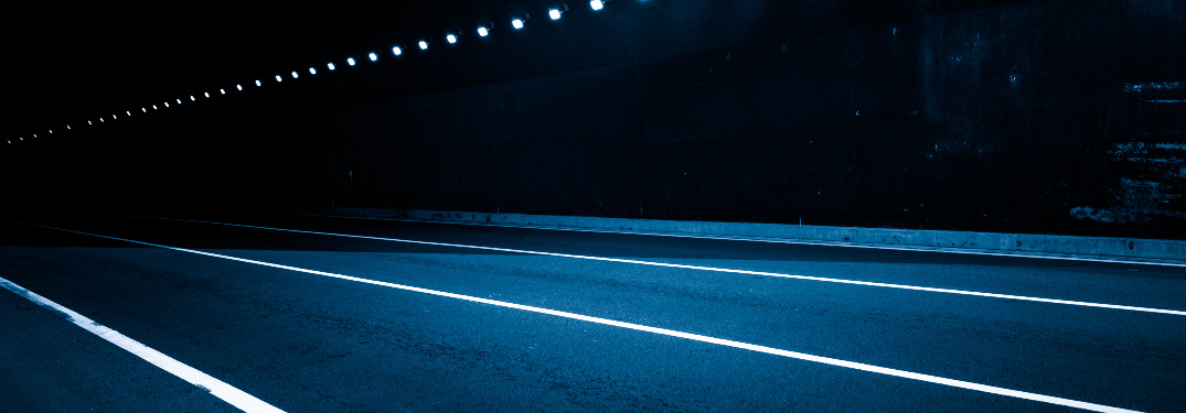 Blue-toned image of an empty road at night