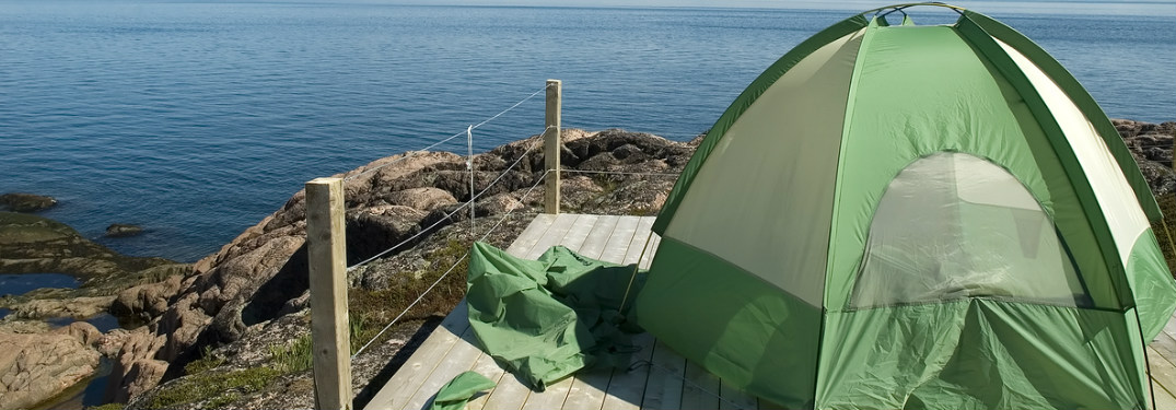 tent set up on a platform overlooking a body of water