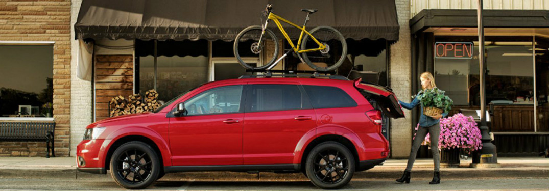 2018 Dodge Journey in red with a yellow bike strapped to the roof rail and an open liftgate