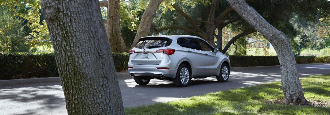 2019 Buick Envision in white driving down a tree-lined street