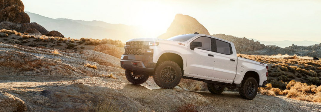 2019 Chevy Silverado in white parked on a gravel path in the mountains