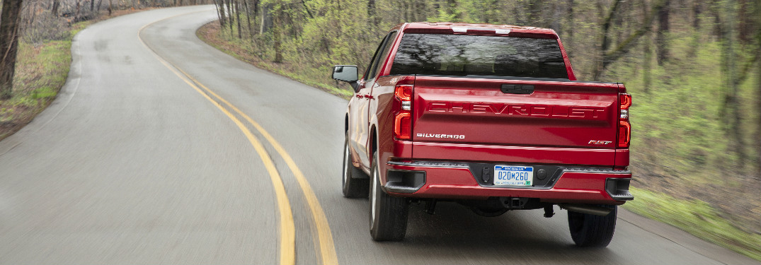 2019 Chevy Silverado in red driving down a winding wooded road
