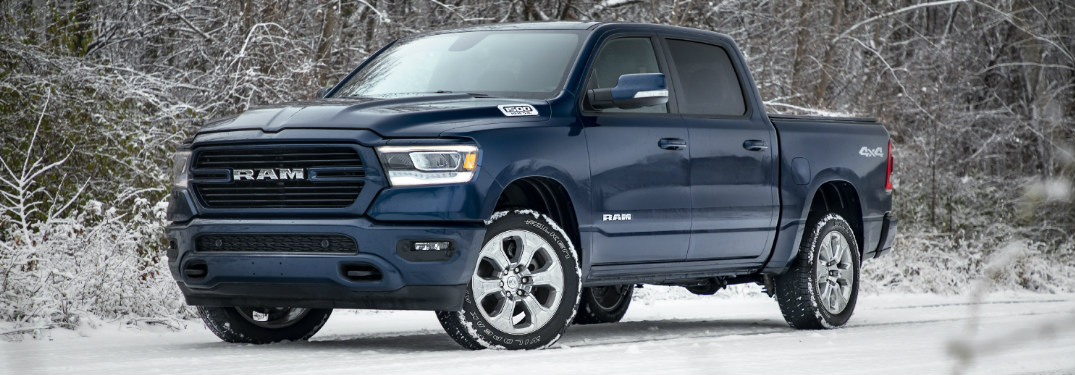 2019 RAM 1500 in blue parked on a snow-covered road near trees