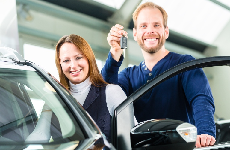 Couple holding keys next to new vehicle