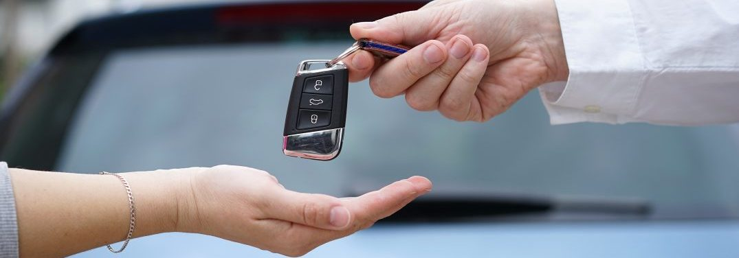Car Dealer Gives The Customer The Car Keys With Car In Backgorun