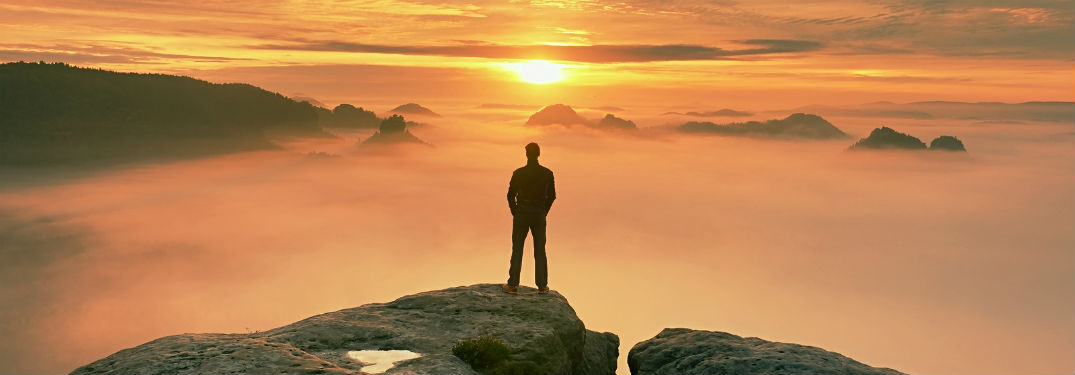 man standing on cliff with fog and sunrise