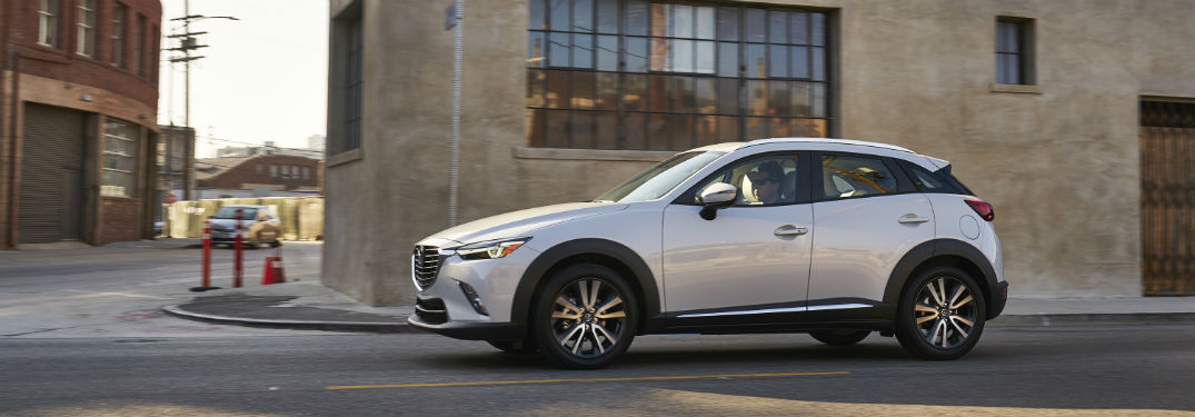 2018 Mazda CX-3 exterior drivers side profile on city road next to beige building