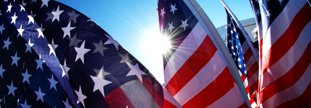 close up of 4 American flags with sun shining in background