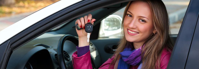 A woman sitting in a car holding a key
