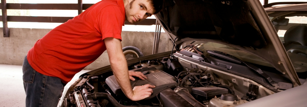 person in a red shirt looking under the hood of their car