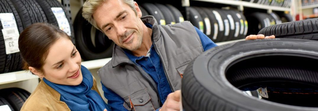 Man and women looking a tires in a tire shop