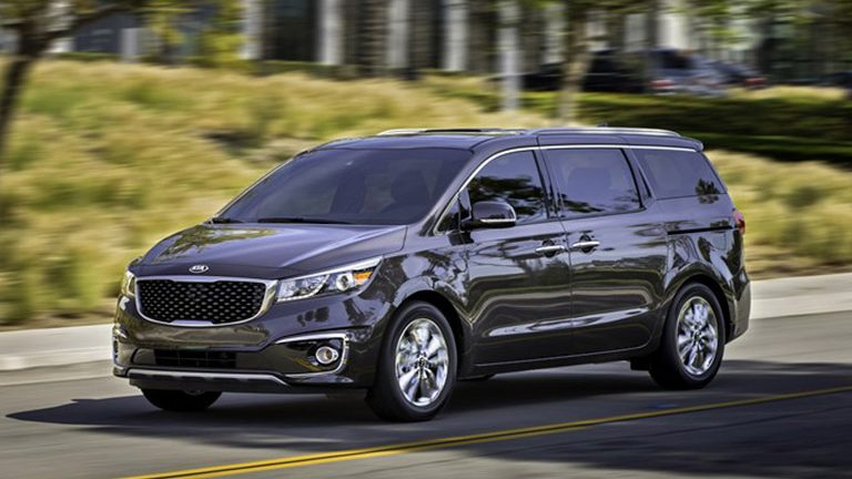 2016 Kia Sedona driving by trees on a highway