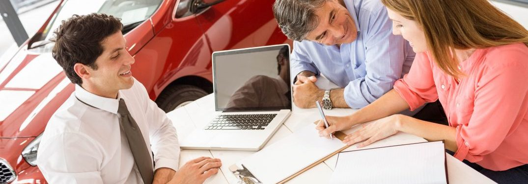 Man and woman signing paperwork in a car dealership with a salesperson sitting across the desk