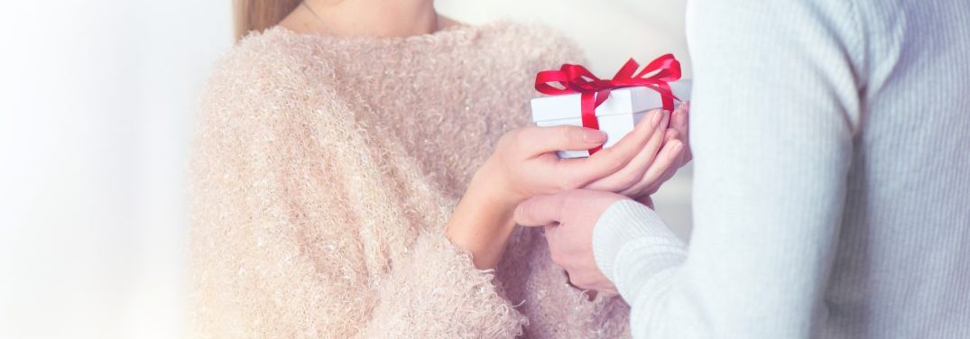 Two People exchanging a gift wrapped in white with a red bow