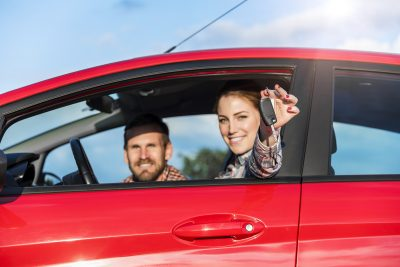 People in a red car, with a woman in the driver seat holding a key fob out of the window