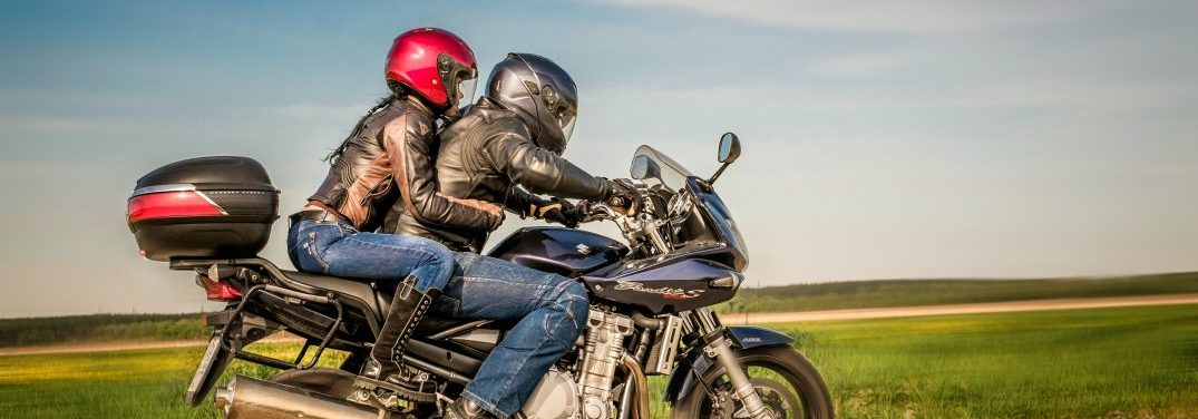 Man and a woman driving on a motorcycle wearing helmets