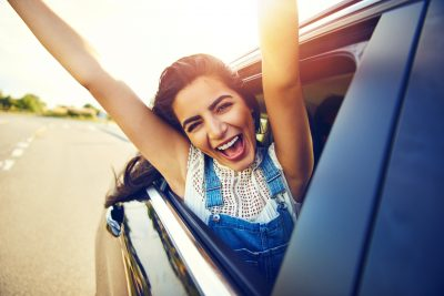 Young woman sticking her head and arms out of a car window with a smile on her face