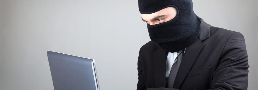 Computer Hacker wearing a balaclava in a suit and tie