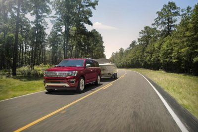 2018 Ford Expedition towing a boat on an open road with trees on the side