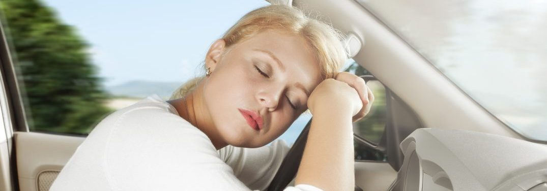 Woman falling asleep at the wheel of a car