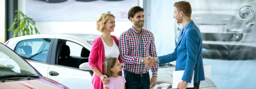 A couple with a child and a salesman at a car dealership