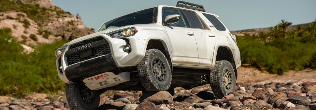 Front driver angle of a white 2020 Toyota 4Runner driving over rocks