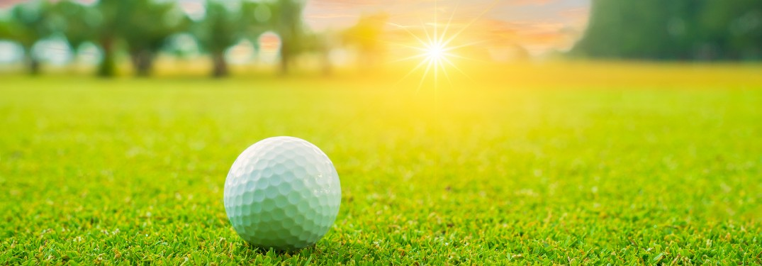 Close up of a golf ball sitting on a golf course with trees and the sun in the background