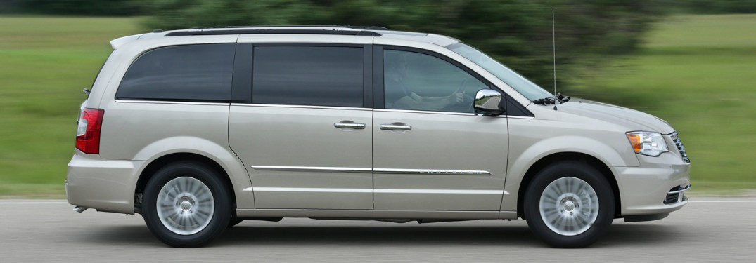 Passenger angle of a white 2016 Chrysler Town & Country driving down a road