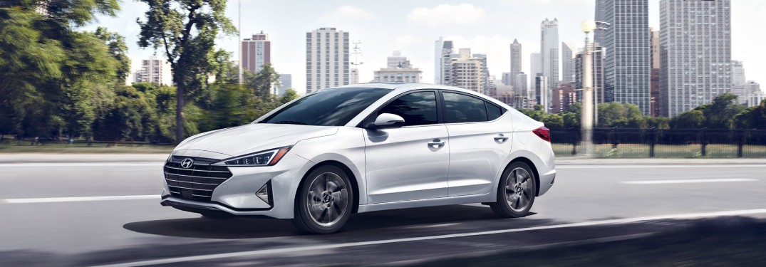 Front driver angle of a white 2020 Hyundai Elantra driving with a city in the background
