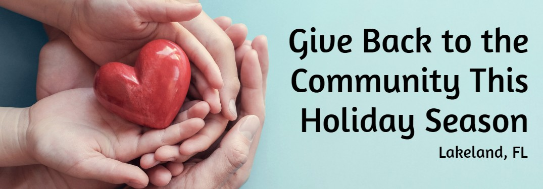 "Hands holding a heart on a blue background with the text ""Give back to the community this holiday season Lakeland, FL"""