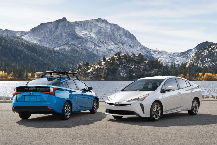 Front driver angle of a white 2019 Toyota Prius parked next to a blue 2019 Toyota Prius in front of a lake