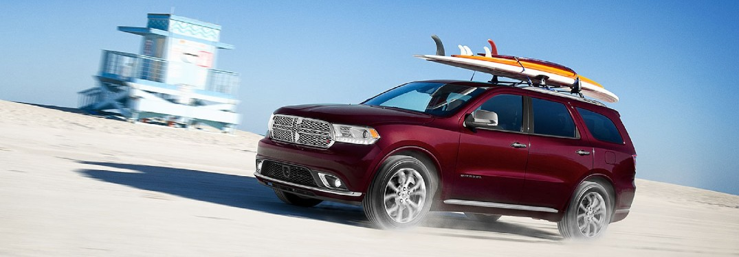 Front driver angle of a red 2020 Dodge Durango with surfboards mounted on its roof rails and driving on a beach