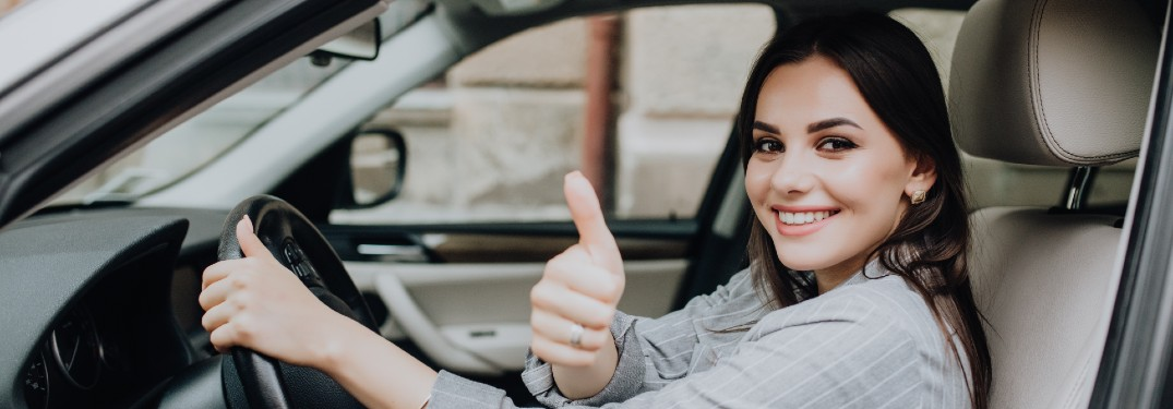 Happy woman in a car giving a thumbs up