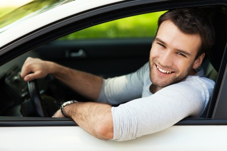 Happy young man sitting in a white car