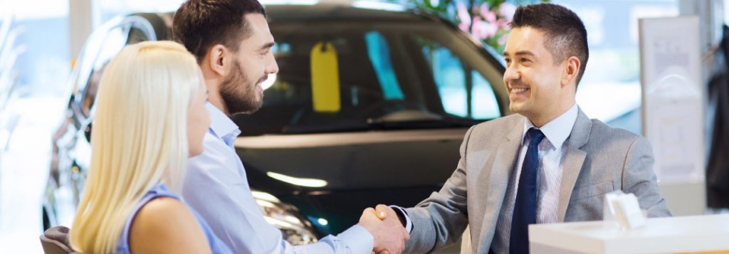 Happy couple shaking hands with a car salesman