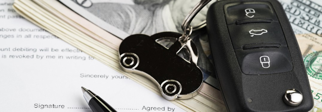 Close up of car keys with cash and a loan application