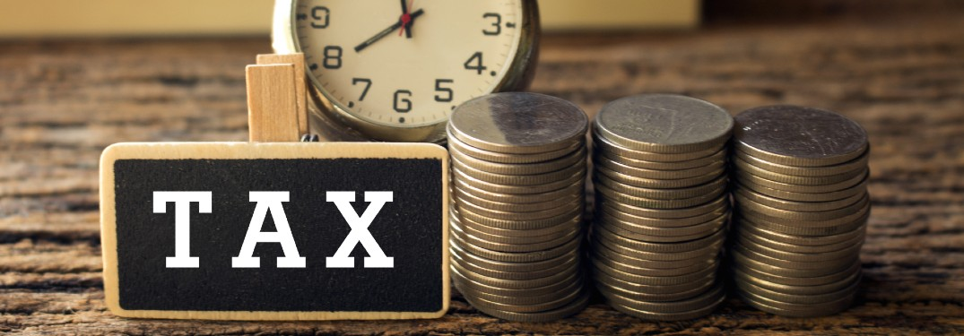 "Close up of coins, a clock, and the word ""Tax"""