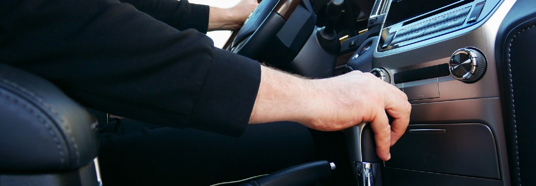 Driver's hand on the gear shift inside a vehicle