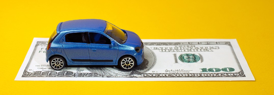 Toy car sitting on a one-hundred dollar bill on a yellow background