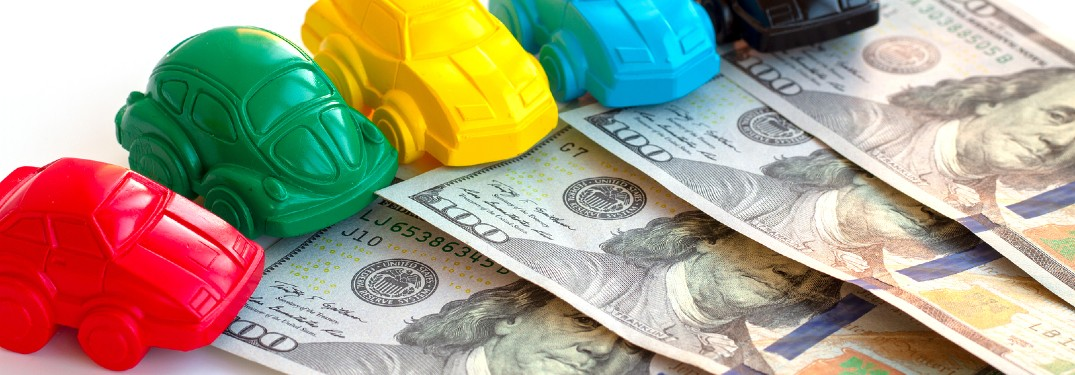 Colorful toy cars on top of one-hundred dollar bills