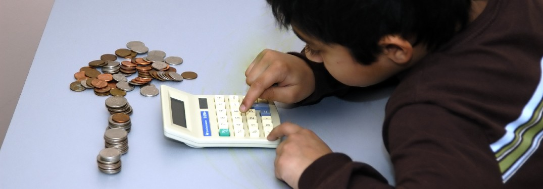 Young boy counting his coins with a calculator