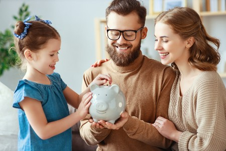 Happy family with a girl putting coins in a piggy bank