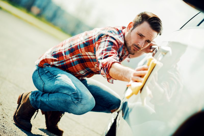 Young man cleaning his car outdoors.Man with a microfiber wipe the car polishing.