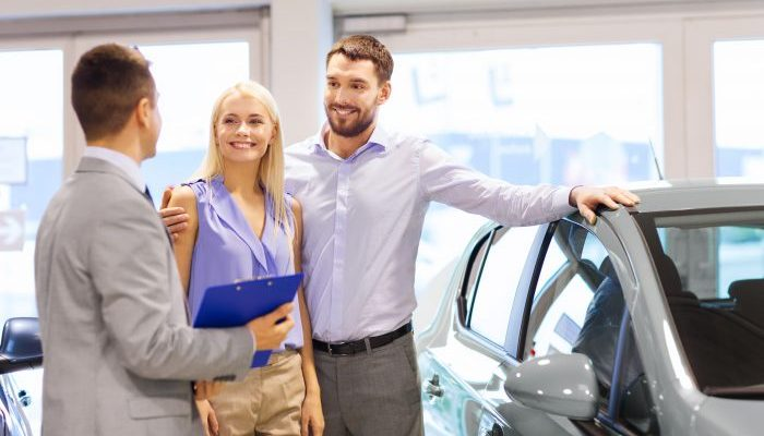 couple browsing a car dealership speaking to a salesman