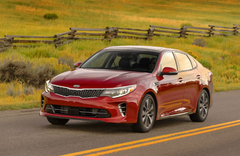 Red Kia Optima driving on country road