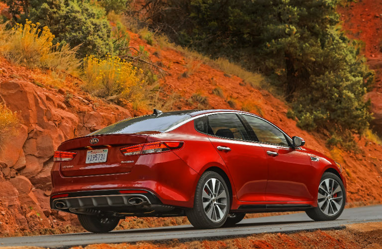 Rear shot of red 2018 Kia Optima driving on autumn day