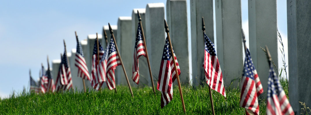 American flags planted near gravestones to commemorate Memorial Day