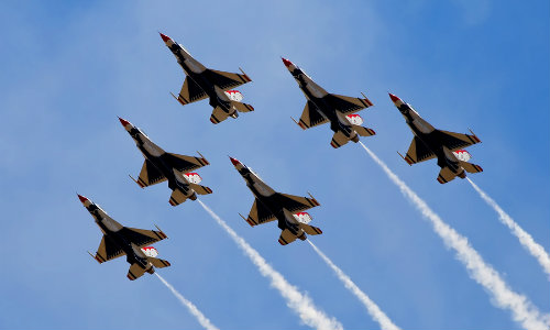Fighter jets executing flyover demonstration in daytime