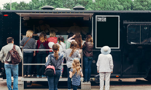 People lined up for food truck in outdoor market
